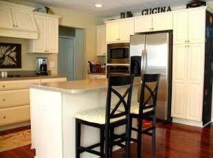 淡黄色的橱柜不仅让厨房显得柔和,而且亮色容易让人保持欢快的心情。与之相配的深色地板和黑色座椅给人另一种沉稳的意境。,厨房,餐厅,现代,简约,餐台,黄色,黑白,