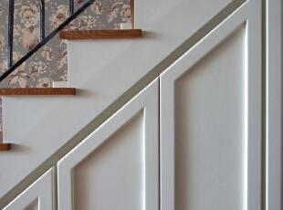 客厅的实景照片  楼梯结构成就了下面的储物柜,柜门为造型隐形状,