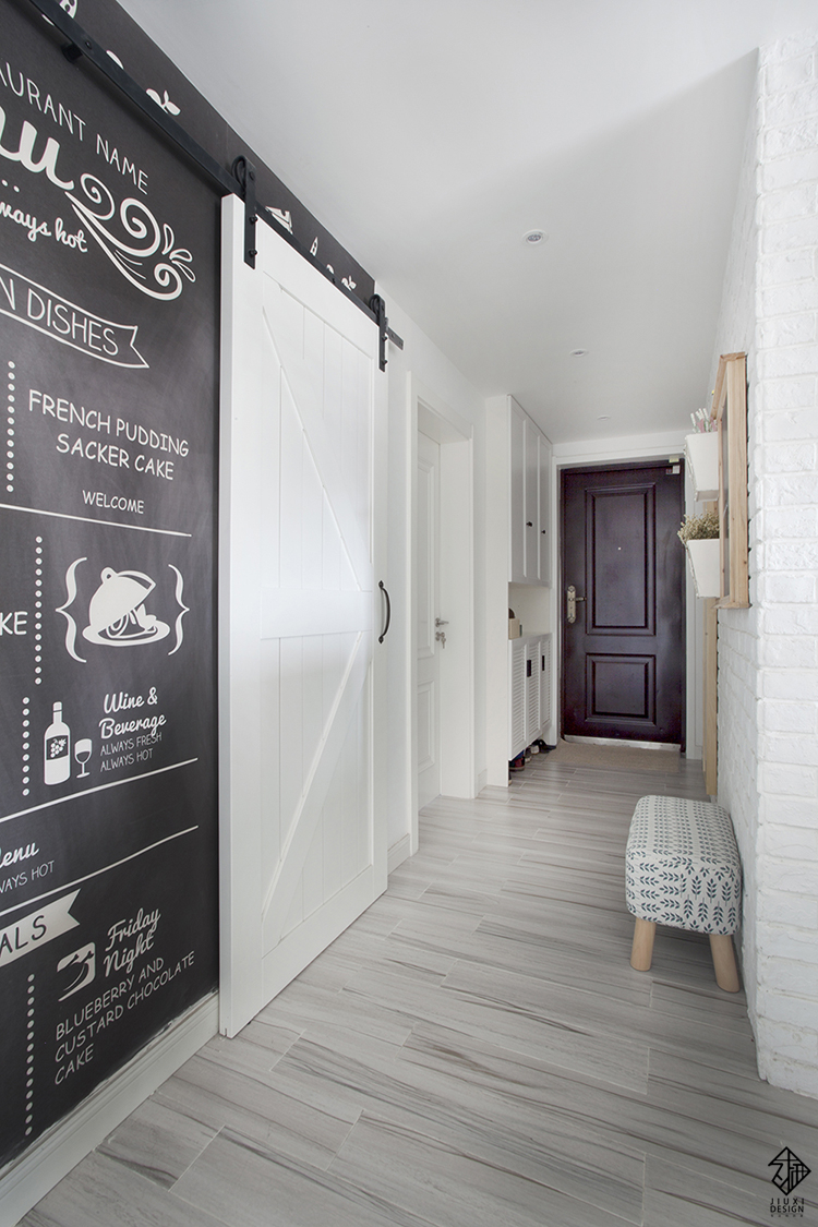 白色的谷仓门与黑板墙装饰墙相得益彰,成为玄关处的一道亮点.