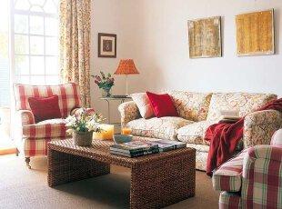 """碎花的布艺沙发,将花团锦簇的田园美感融入到空间中;红色格子图案的沙发,赋予经典韵味。色彩缤纷的鲜花和自然优雅的家具,组成了这个温馨而质朴的""""乡村""""客厅。"""