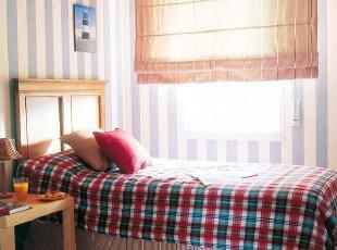 以蓝色和白色为主调的墙面,让卧室环绕着温馨的气息,实木家具和灯饰的采用,使空间更具亲和力,散发出淡淡的乡村自然气息。
