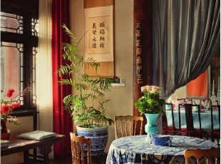 正厅里,桌上红色的插花作品是日本花艺师夏本为春节专门设计的,后面的花瓶式烛台购于欧洲,是欧洲人想象中的中国样式。后面挂的那幅金色现代画出自一位法国女士之手,是她送给Alan的礼物。,265平,1000万,中式,大户型,
