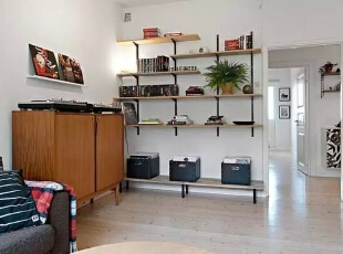客厅的一角在墙面上做了定制的置物架,男主人平时喜欢音乐,一些CD、书籍放这里,既解决了收纳问题,空白的墙面也有了装饰作用。,51平,65万,简约,一居,