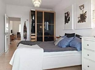 卧室沿用了客厅白色深灰色搭配的主色调,因面积小,天花板没有做复杂的吊顶,一盏水晶灯满足了照明作用,床头墙面并没有放置二人的婚纱照,两个服装设计效果图的画框,印证了女主人对这个行业的喜爱。,51平,6万,简约,一居,