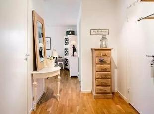 在房间转角的地方一侧的墙面摆放白色的古典半圆边柜上面放上框镜和灯饰,另一侧是木质的收纳斗柜看起来非常的复古。,60平,4万,现代,一居,